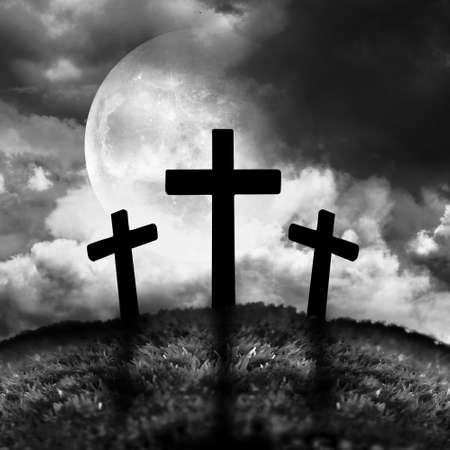 Silhouet van drie kruisen op een heuvel met een maan achter hen
