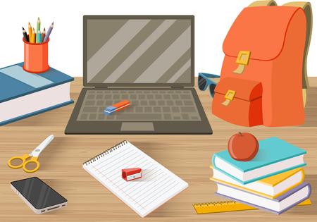 Stół studencki z książkami i innymi przedmiotami.