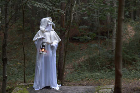 Plague doctor in forest with lantern in hands