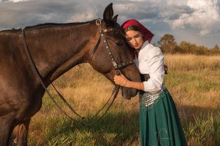 bella zingara con un cavallo nel campo in estate Archivio Fotografico
