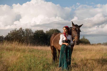 bella zingara con un cavallo nel campo in estate