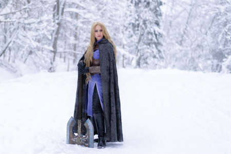 warrior girl with blond hair and big ax in winter forest Zdjęcie Seryjne