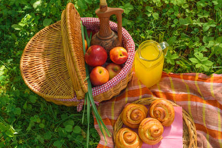 Picnic in nature. Picnic basket with fruit decanter juice and buns