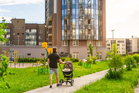 Father with son in a stroller walk along the sidewalk in the vicinity of the city. A child in a baby carriage and a man in the background of nature. Family holiday on a vacations.
