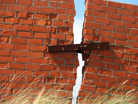 earthquake: Crack in the brick fence, connected by a piece of iron