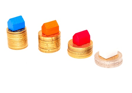 mortgaging: Miniature houses on euro coins Stock Photo