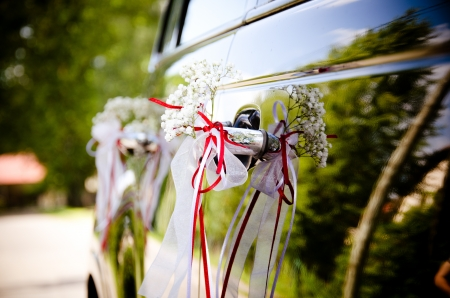 black wedding car decorated by flowers and red ribbons photo