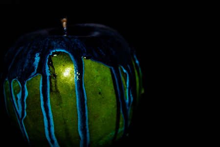 Red apple with dripping blue paint. Minimal food concept.
