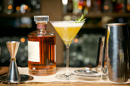 An exquisite Duke Tulip cocktail On a wooden tray. Against the background of a restaurant