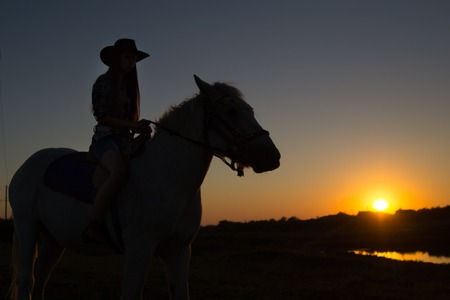 black cowgirl: A cowgirl riding a horse in the middle of a grassy field on a ranch is silhouetted against the afternoon sun.