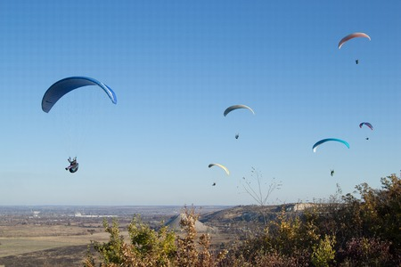 pilot light: Paraglider flying in the sky over the slope