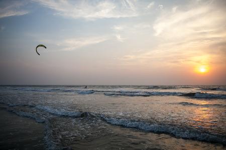 Beautiful ocean sunset, kitesurfer on the waves Stock Photo