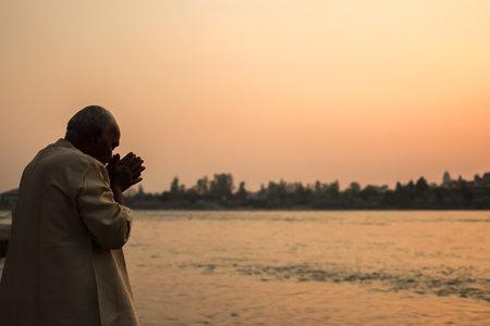 Rishikesh, India - March 23rd, 2015. Man praying on the riverbank of Ganga river in Rishikesh