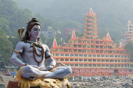 Statue of Shiva sitting in meditation on the riverbank of Ganga in Rishikesh, Tera Manzil Temple, Trayambakeshwar in background