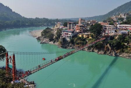 Rishikesh, India - November, 5th, 2017. View of Ganga river embankment and Lakshman Jhula bridge in Rishikesh