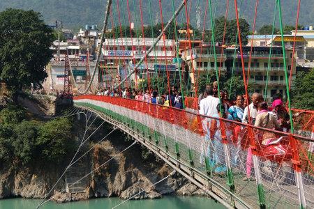 Rishikesh, India - November, 5th, 2017. People crossing Laxman Jhula bridge.