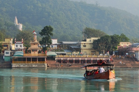 Rishikesh, India - November, 5th, 2017. Beautiful view of the Ganga river embankment in Rishikesh. People cross the river Ganga by boat Editorial