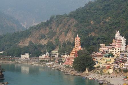 Rishikesh, India - November, 9th, 2017. View of Ganga river embankment, Lakshman Jhula bridge and Tera Manzil Temple, Trimbakeshwar in Rishikesh Stock Photo