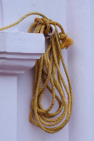 Yellow rope hanging on the wall Stock Photo