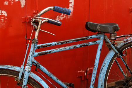 Mumbai, India - February, 25th, 2017. Vintage blue bicycle on the red background