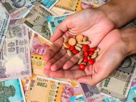 Womans hands holding pills over 10, 20, 50, 100, 200, 500 and 2000 Indian rupees, old and new notes. Stock Photo