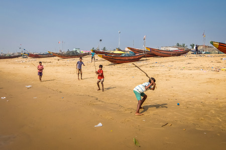 Puri, India - Circa January, 2018. Kids playing cricket on the sandy beach with fishing boats on the background.