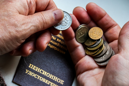 Woman's hands holding russian coins over the pension certificate. Russian translation - Ministry of Social Protection of Population of Russian Federation. Pension Certificate.