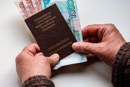 Womans hands holding russian pension certificate and russian rubles. Russian translation - Ministry of Social Protection of Population of Russian Federation. Pension Certificate. Stok Fotoğraf