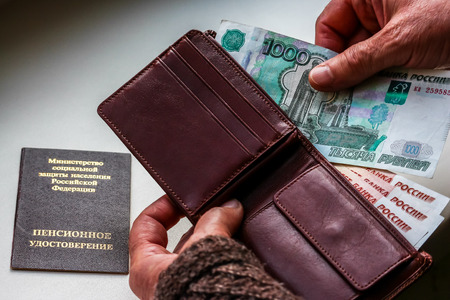Woman's hands holding wallet with russian rubles, russian pension certificate in background. Russian translation - Ministry of Social Protection of Population of Russian Federation. Pension Certificate.