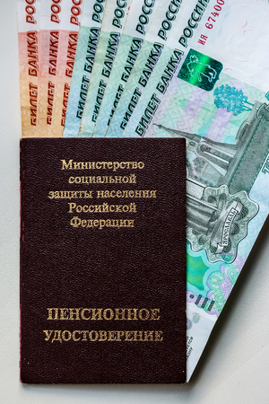 Russian pension certificate and currency (banknotes).Russian translation - Ministry of Social Protection of Population of Russian Federation. Pension Certificate.
