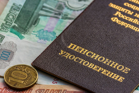 Russian pension certificate and currency (banknotes and coins). Russian translation - Ministry of Social Protection of Population of Russian Federation. Pension Certificate.