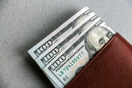 Closeup view of wallet with one hundred and fifty dollar banknotes.