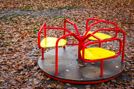 View of the carousel on children's playground. Yellow autumn leaves lying on the ground.