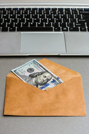 Closeup view of envelope with one hundred dollar banknote and laptop keyboard.
