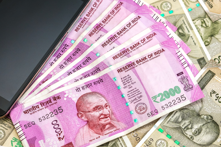 Close up view of brand new indian 2000 rupees banknotes and smarthphone. 500 rupee banknotes in background.