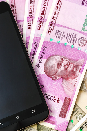 Close up view of brand new indian 2000 rupees banknotes and smarthphone. 500 rupee banknotes in background. Stock Photo