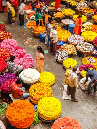 Bangalore, India - Circa January, 2018. Flower sellers and their customers at colorful KR Market in Bangalore.