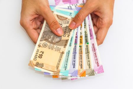 Female hands holding brand new 10, 50, 100, 200, 500 and 2000 indian rupees banknotes.