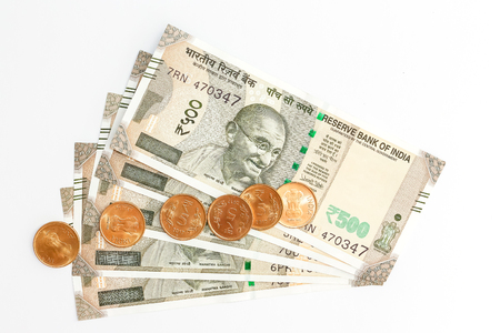 Close up view of brand new indian 500 rupees banknotes and coins on white background.