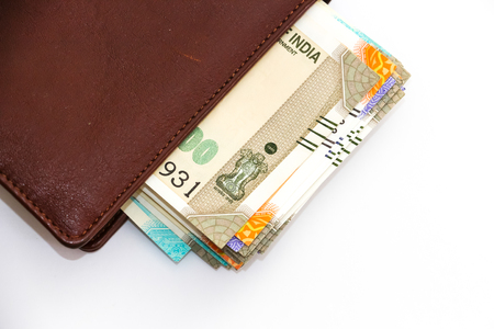Close up view of wallet with brand new indian 50, 100, 200, 500 rupees banknotes on white background.