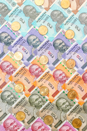 Close up view of brand new indian 10, 50, 100, 200, 500 and 2000 rupees banknotes and five rupee coins. Colorful money ornamental background. Stock Photo
