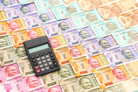 Close up view of calculator over  brand new indian 10, 50, 100, 200, 500 and 2000 rupees banknotes. Colorful money pattern.
