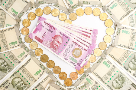 Close up view of new indian 500 and 2000 rupees banknotes and coins. Heartshape concept.