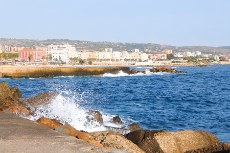 Civitavecchia, Italy - Circa  September 2017. View View of the embankment of Civitavecchia with green palm trees, blue sky, old typical roman houses and promenade along the coast in Lazio, Italy.