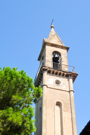 Bell tower of catholic church (Chiesa di San Leopoldo) in small town Vada on the coast of the Ligurian Sea. Province Livorno, Tuscany region of Italy