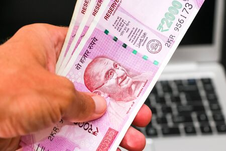 Hand holding brand new indian 2000 rupees banknotes, laptop in background.