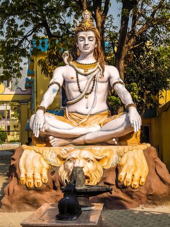 Statue of Shiva sitting in meditation on the riverbank of Ganga in Rishikesh.