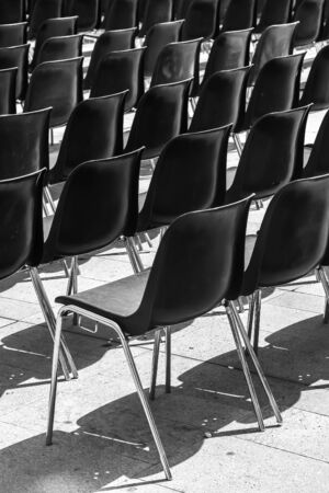 Rows of empty black chairs, prepared for event.