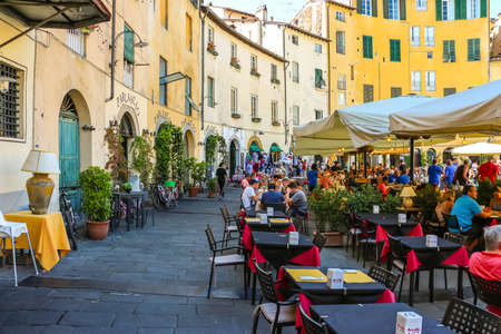 Lucca, Italy - Circa September 2018. Tourists visit famous square Piazza dell'Anfiteatro in Lucca.