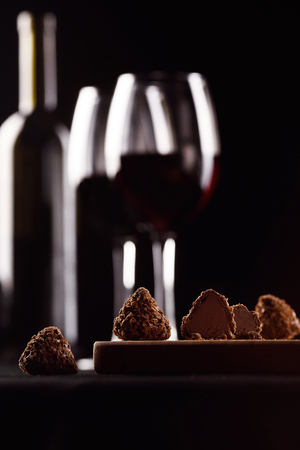 chocolates, wine with the glass on black background in blur Stock Photo